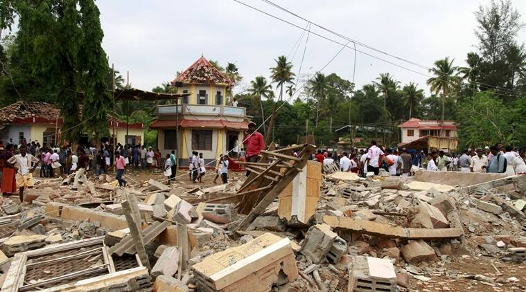 People walk past debris after a fire broke out at a temple in Kollam in the southern state of Kerala, India, April 10, 2016. A huge fire swept through a temple in India's southern Kerala state early on Sunday (April 10), killing nearly 80 people and injuring over 200 gathered for a fireworks display to mark the start of the local Hindu new year. REUTERS/Sivaram V