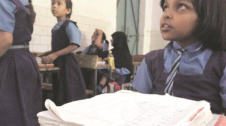 In the absence of notebooks, students, like nine-year-old Saima (above, right), tear unused pages from their old books to use this year. Express photo by Nikhil M Babu - See more at: https://indianexpress.com/article/education/mcd-students-for-70000-children-no-bank-account-no-money-2758203/#sthash.Q4wrm0V7.dpuf