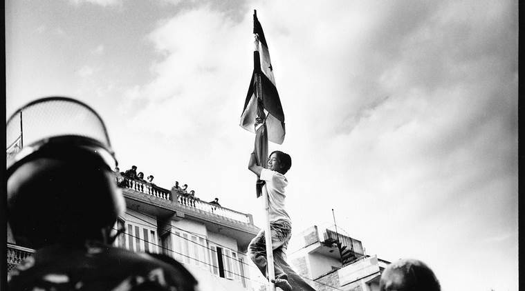 A Demonstrator climbs a flag pole and hangs over police lines at a mass rally aimed at pressuring King Gyanendra to step down in Chabahil on the Kathmandu ring-road.