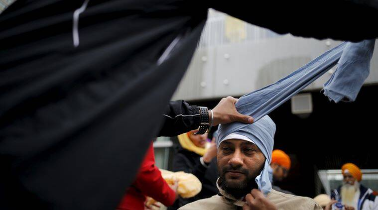 A man has his head wound with a turban during Khalsa Day festivities, also known as Vaisakhi, in front of city hall in Toronto, Canada April 24, 2016. REUTERS/Chris Helgren