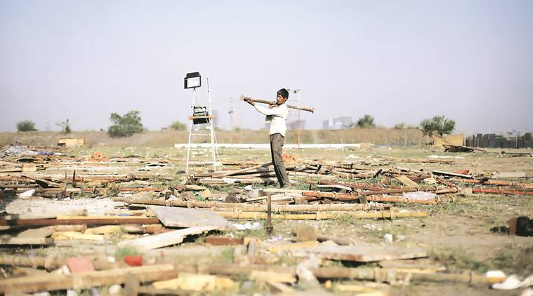 Workers remove construction material from the site of the World Cultural Festival along the Yamuna Flood plains on Tuesday. Express photo by Oinam Anand. 12 April 2016