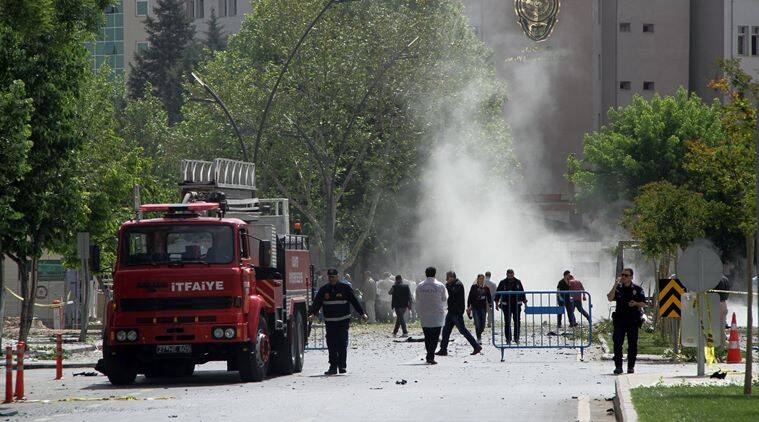 Security officers and firefighters work moments after an explosion outside the Police headquarters in Gaziantep, Turkey, Sunday, May 1, 2016. A car bomb struck the entrance of a Turkish police station Sunday in the southern city of Gaziantep, killing a policeman and injuring over 20 other people, an official said. (Depo Photos via AP) TURKEY OUT