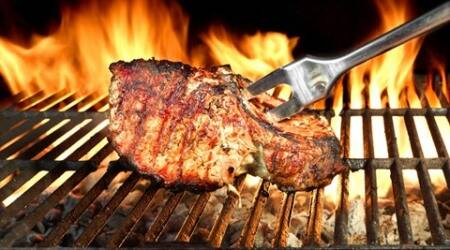 Meat Chop Cooked On The Barbecue Grill. Flame Of Fire In The Background.