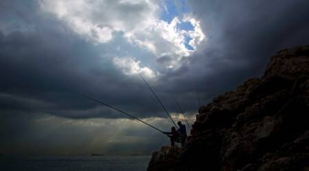 Lebanese men cast their fishing poles from a rocky coastal area along the Beirut coastline in Lebanon, Friday, May 6, 2016. Beirut's coastline has been for thousands of years a vital source of sustenance for local residents but privatization and pollution have now made it increasingly difficult to scrape by on catches from the Mediterranean Sea. (AP Photo/Hassan Ammar)