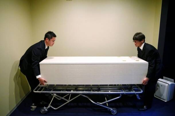 Staff members remove a coffin from a room of the 'Corpse Hotel' in Kawasaki