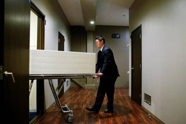 A staff member removes a coffin from a room of the 'Corpse Hotel' in Kawasaki, Japan