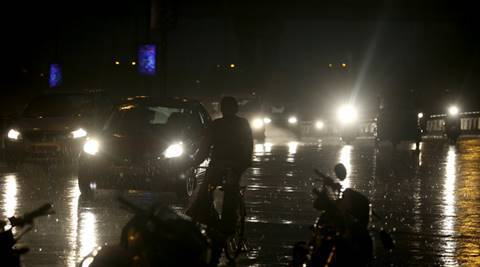 A Vehicle and people move during rain in New Delhi on Monday. Express Photo By Amit Mehra 23 May 2016