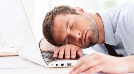 Side view of young man in shirt and tie sleeping while sitting at his working place