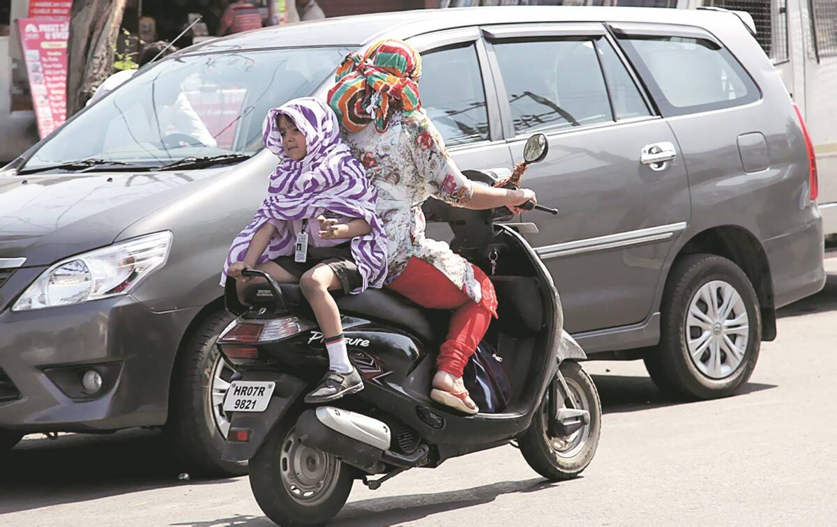 Mother protecting his child from heat during summer. Express photo by Jaipal Singh