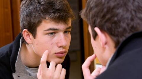 Teenager examining  acne  in the mirror