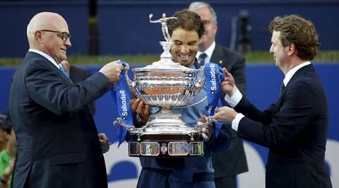 Rafael Nadal of Spain raises up the Barcelona Open trophy after defeating Kei Nishikori of Japan, next to Banc Sabadell President Josep Oliu and Carlos Godo in Barcelona