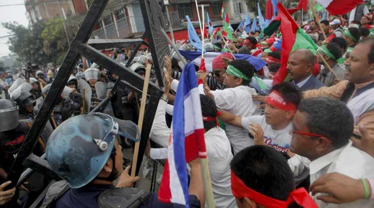 Supporters of Nepal's minority ethnic group wearing headbands with the name of the group try to break through a police cordon, as they protest in a main street leading to the prime minister's office in Kathmandu.(AP photo)