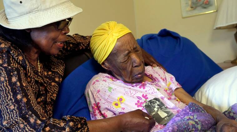 FILE - In this Monday, June 22, 2015 file photo, Lois Judge, left, holds a 1939 photo of her aunt Susannah Mushatt Jones, right, during an interview in Jones' room at the Vandalia Avenue Houses, in the Brooklyn borough of New York. Jones, the world's oldest person, has died in New York at age 116. Robert Young, a senior consultant for the Gerontology Research Group, says Jones died at a senior home in Brooklyn Thursday night, May 12, 2016. He said she had been ill for the past 10 days. (AP Photo/Richard Drew, File)