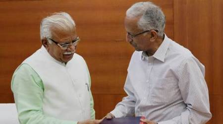 Chandigarh: Haryana Chief Minister Manohar Lal Khattar (L) receives a report from former DGP, UP and Assam, Parkash Singh, in Chandigarh on Friday. Singh was appointed chairman of a committee to inquire into allegations of omissions and commissions on part of civil and police officials during the Jat quota agitation in Haryana in February. PTI Photo(PTI5_13_2016_000047B)