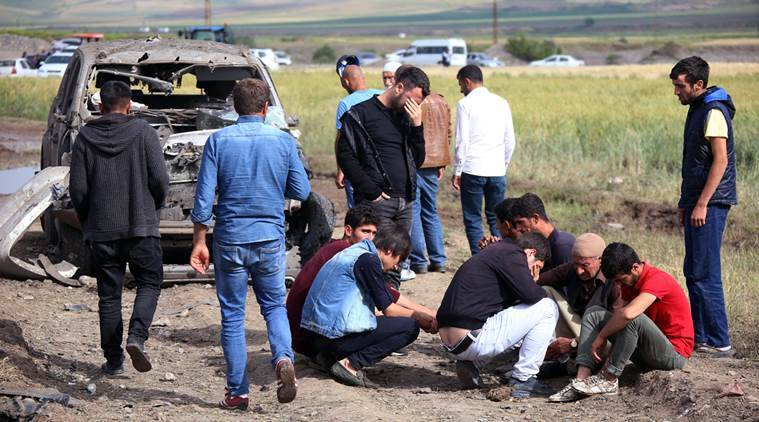 People react near Thursday's explosion site in Sarikamis district outside Diyarbakir, Turkey, Friday, May 13, 2016. A Turkish official said four Kurdish rebels were killed while loading explosives onto a truck in southeastern Turkey late Thursday,  after a separate blast targeting the military in Istanbul wounded eight. (AP Photo/Mahmut Bozarslan)