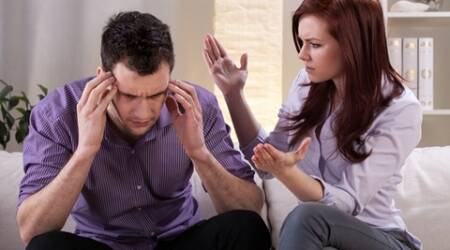 Man getting a headache in the middle of marital quarrel