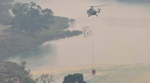 Srinagar: Indian Air Force Helicopter collects water from Koteshwar dam during the rescue operation to control fire which broke out in the forests of Garhwal range in Srinagar, Uttrakhand on Sunday. PTI Photo(PTI5_1_2016_000130A)