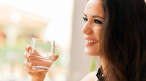 Beautiful young lady drinking water in restaurant