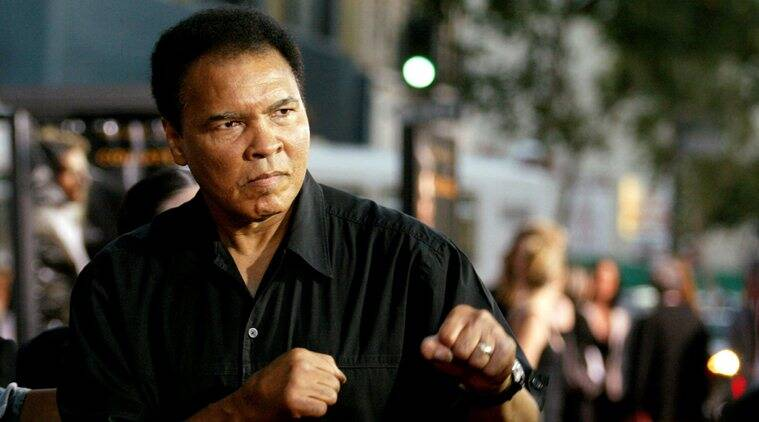 "Boxing legend Muhammad Ali (R) jabs at photographers while arriving at the Orpheum Theatre for the premiere of the film ""Collateral"" in Los Angeles in this August 2, 2004 file photo. REUTERS/Robert Galbraith/File Photo"