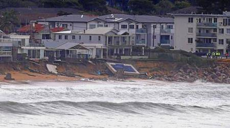 Officials stand near a swimming pool and houses that suffered damage after severe weather that brought strong winds and heavy rain to the east coast of Australia, at Collaroy beach in Sydney, Australia, June 6, 2016.      REUTERS/David Gray