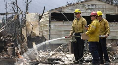 Firefighters water down hot spots Sunday June 26, 2016 at a home destroyed by a fire that swept through the area near Lake Isabella in Squirrel Valley, Calif. The deadly wildfire in central California has burned hundreds of homes. (AP Photo/Rich Pedroncelli)