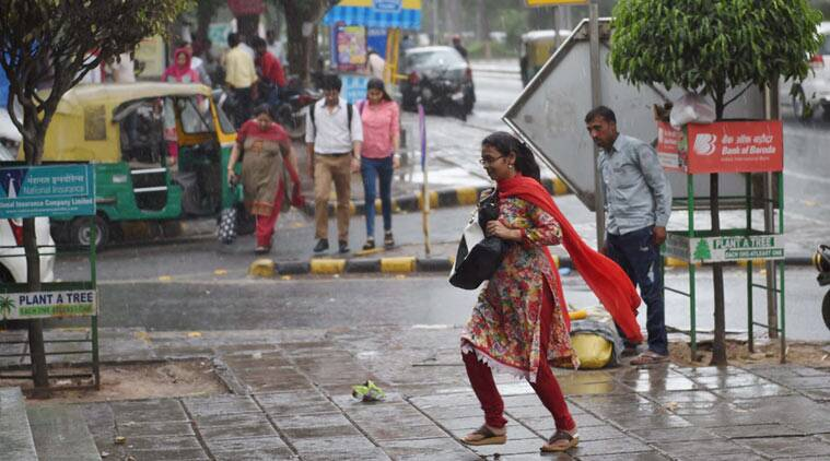 People rush for cover to a metro station during welcome showers in New Delhi on Friday. (Source: PTI)