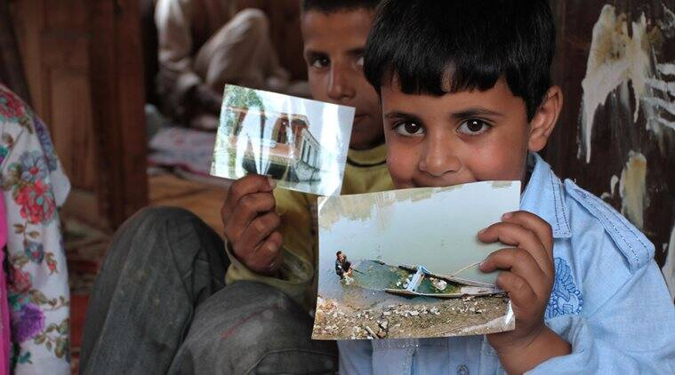 Grandchildren of display pictures of Ghulam Muhammad Guroo, a 60-year-old boatman drowned in Jhelum river in Srinagar while saving three tourists after the Shikara they were riding capsized last week. Express Photo by Shuaib Masoodi