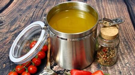 Desi ghee or clariified liquid butter in steel jar with cherry tomatoes and peppers