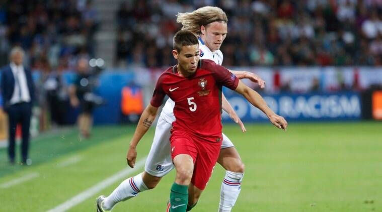 Portugal's Raphael Guerreiro runs with the ball past Iceland's Birkir Bjarnason during the Euro 2016 Group F soccer match between Portugal and Iceland at the Geoffroy Guichard stadium in Saint-Etienne, France, Tuesday, June 14, 2016. (AP Photo/)