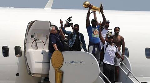 Off the plane but still sky-high, LeBron James brings  title home