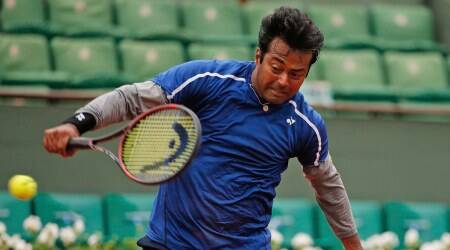 India's Leander Paes hits a return when playing with Switzerland's Martina Hingis in the mixed doubles final of the French Open tennis tournament against India's Sania Mirza and Croatia's Ivan Dodic at the Roland Garros stadium in Paris, France, Friday, June 3, 2016. (AP Photo/Alastair Grant)