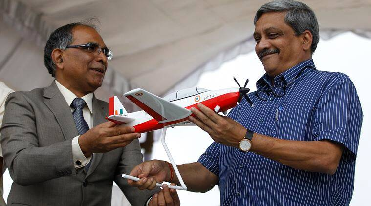 Indian Defence Minister, Manohar Parrikar, receives a model of indigenous prototype trainer aircraft, HTT-40 (Hindustan Turbo Trainer– 40), from Chairman of Hindustan Aeronautics Limited, T. Suvarna Raju, in Bangalore, India, Friday, June 17, 2016. (AP Photo/Aijaz Rahi)