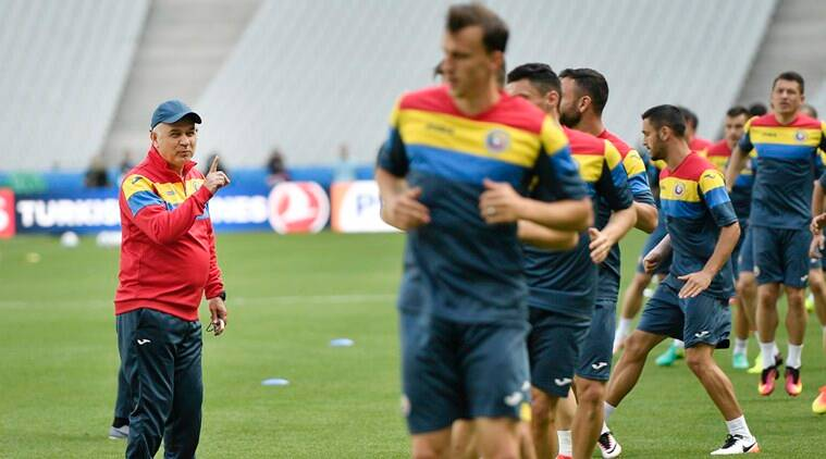 Romania coach Anghel Lordanescu , left, smiles to his players during a training session at the Stade de France, Saint-Denis, north of Paris, France, Thursday, June 9, 2016. France will face Romania in the Euro 2016 Group A opening soccer match in Saint-Denis on Friday, June 10, 2016. (AP Photo/Martin Meissner)