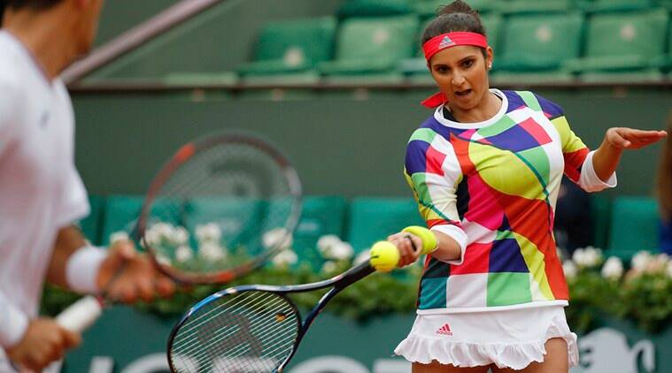 India's Sania Mirza, right, and Croatia's Ivan Dodic return the ball in the final of the mixed doubles match of the French Open tennis tournament against Switzerland's Martina Hingis and India's Leander Paes at the Roland Garros stadium in Paris, France, Friday, June 3, 2016. (AP Photo/Alastair Grant)