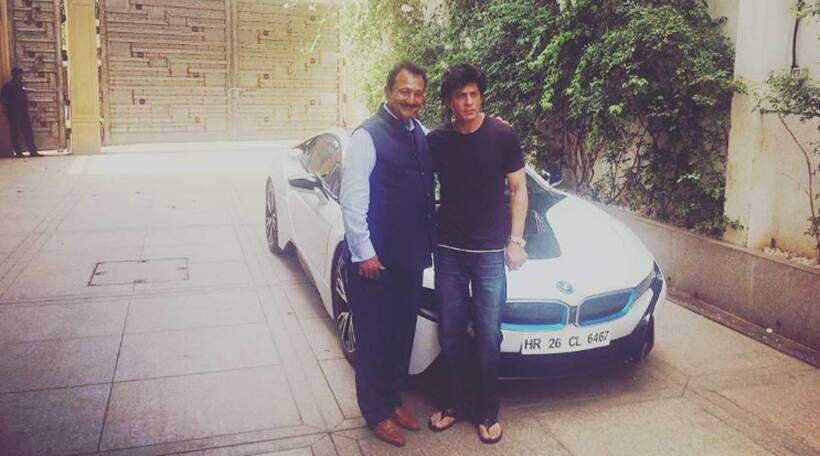 Shahrukh Khan standing next to his white hybrid BMW i8