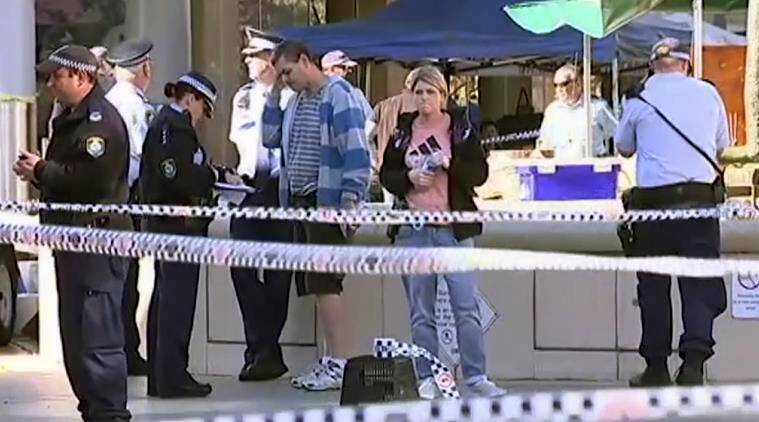 In this image made from video provided by Australian Broadcasting Corporation, police work behind tape at a shopping mall in Sydney, Thursday, June 9, 2016. Police officers opened fire on a man armed with a carving knife in a Sydney shopping mall on Thursday, wounding the man and three women aged between 60 and 80, police said. (Australian Broadcasting Corporation via AP) ** AUSTRALIA OUT **