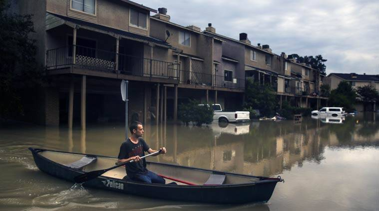 canoes past flooded townhouses in the Forest Cove neighborhood as he tries to get to his home Thursday, June 2, 2016 near Kingwood, Texas. Parts of Texas have been inundated with rain in the last week, and more than half of the state is under flood watches or warnings, including the counties near Fort Hood. (Source: AP)