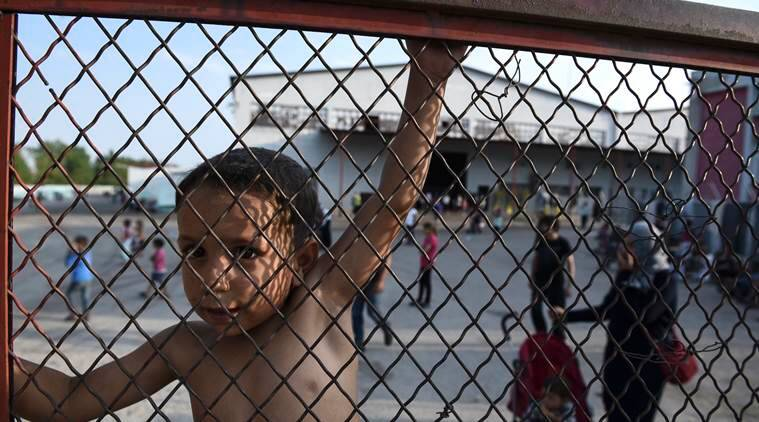 A child stands behind a fence during a protest against the living conditions at the Oreokastro camp, near the northern town of Thessaloniki, Greece, on Saturday, June 25, 2016. More than 50,000 migrants remain stranded in Greece following European border closures and an agreement reached in March between the European Union and Turkey to deport newly arrived migrants traveling across the Aegean Sea. (AP Photo/Giannis Papanikos)