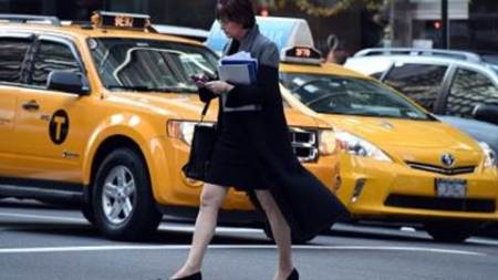 A woman uses her smartphone while crossing a street corner