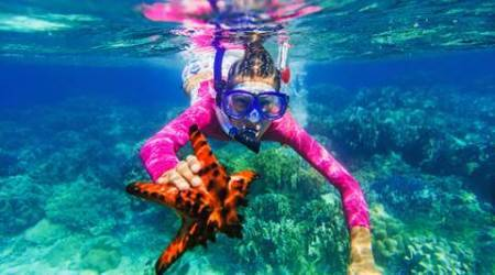Underwater photo of happy girl with a giant starfish