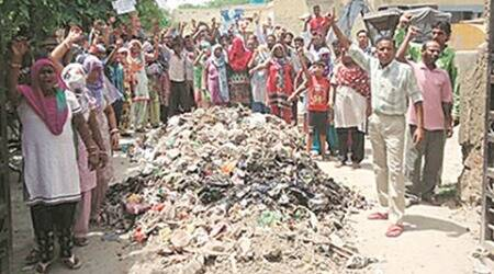 Abohar: Demanding pay, sanitation workers pile up garbage in front of govt offices