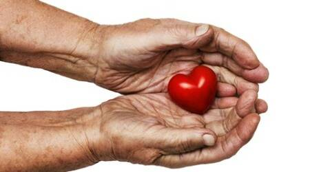 elderly woman keeping red heart in her palms isolated on white background, symbol of care and love