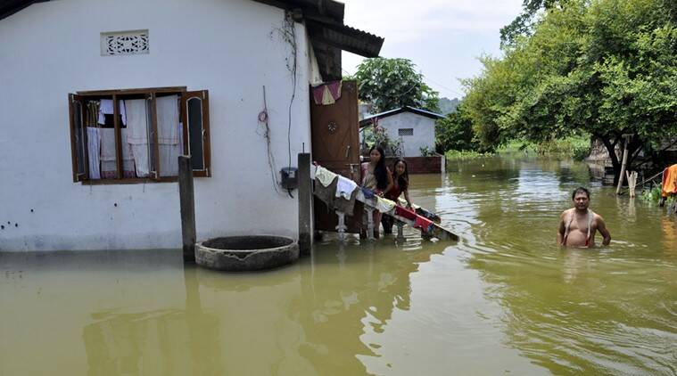Villagers out side their submerged house in flood water in the flooded affected Rajabari village in Kamrup district of Assam on Thursday 28th July 2016.Almost 16 district of Assam is under flood water .Photo-DASARATH DEKA