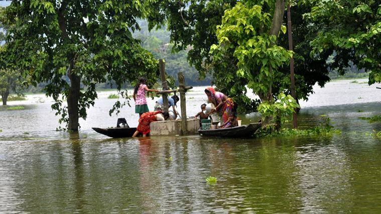 Villagers by standing on boat collect water from a well in the flooded affected Rajabari village in Kamrup district of Assam on Thursday 28th July 2016.Almost 16 district of Assam is under flood water .Photo-DASARATH DEKA
