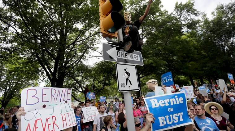 A supporter of Sen. Bernie Sanders, I-Vt., yells at delegates over fence after climbing a light pole in Franklin Delano Roosevelt Park in Philadelphia, Tuesday, July 26, 2016, during the second day of the Democratic National Convention. (AP Photo/Matt Slocum)