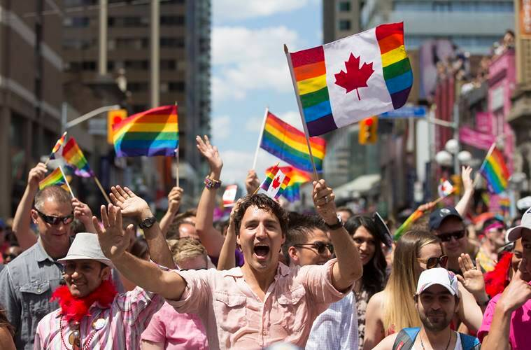 Prime Minister Justin Trudeau waves a flag as he takes part in the annual Pride Parade in Toronto on Sunday, July 3, 2016. (Mark Blinch/The Canadian Press via AP)