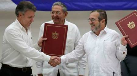 In this Thursday, June 23, 2016 photo, Colombian President Juan Manuel Santos, left, and Commander of the Revolutionary Armed Forces of Colombia or FARC, Timoleon Jimenez, right, shake hands during a signing ceremony of a cease-fire and rebel disarmament deal, in Havana, Cuba. The deal moves Colombia closer to ending a 52-year war that has left more than 220,000 people dead. Pictured in the center is Cuba's President Raul Castro. (AP Photo/Ramon Espinosa)