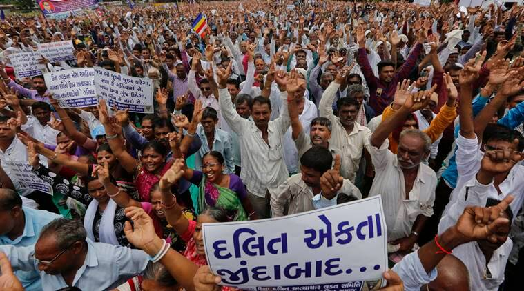 "Hundreds of members of India's low-caste Dalit community take a pledge not to remove cattle carcass as they gather for a rally to protest against the attack on their community members in Ahmadabad, India, Sunday, July 31, 2016.Dalits have been protesting after four men belonging to their community were beaten while trying to skin a dead cow in Una in western Gujarat state early this month. Placard in Gujarati, front, reads, ""Long Live Dalit Unity"". (AP Photo/Ajit Solanki)"