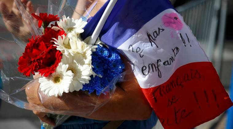 A woman carries blue, white and red flowers and a French flag as a tribute to victicms two days after an attack by the driver of a heavy truck who ran into a crowd on Bastille Day killing scores and injuring as many on the Promenade des Anglais, in Nice, France, July 16, 2016. REUTERS/Pascal Rossignol