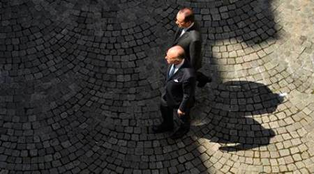 French President Francois Hollande, top, and his Interior Minister Bernard Cazeneuve, arrive to  take part in a minute's silence at the Interior Ministry in Paris, in tribute to the 84 victims of the Nice truck attack, Monday, July 18, 2016.  France is holding a national moment of silence for 84 people killed by a truck rampage in Nice, and thousands of people are massed on the waterfront promenade where Bastille Day celebrations became a killing field. (Bertrand Guay/Pool Photo via AP)